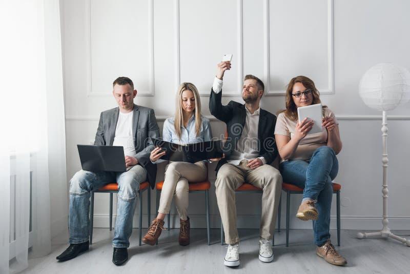 Grupp av idérikt folk som sitter på stolar i väntande rum fotografering för bildbyråer
