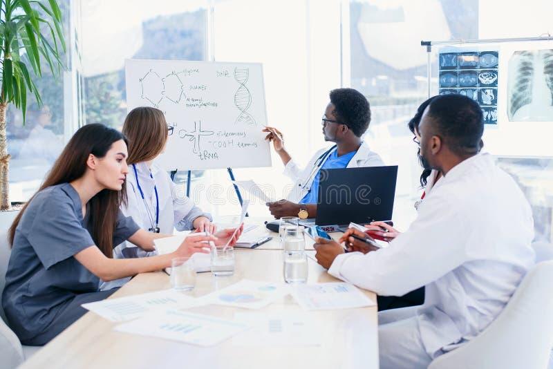 Grupp av ilnternatiomal doktorer eller allmäntjänstgörande läkare med mentormöte och taanmärkningar på sjukhusrum royaltyfria bilder
