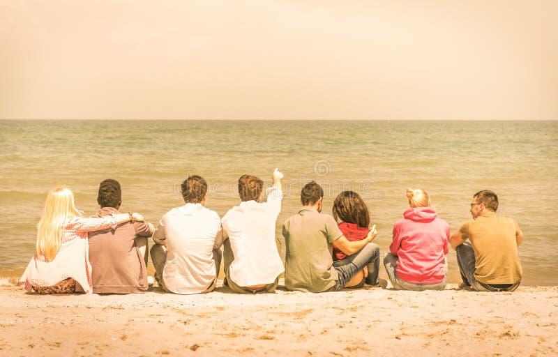 Grupp av internationella blandras- vänner som sitter på stranden arkivfoton