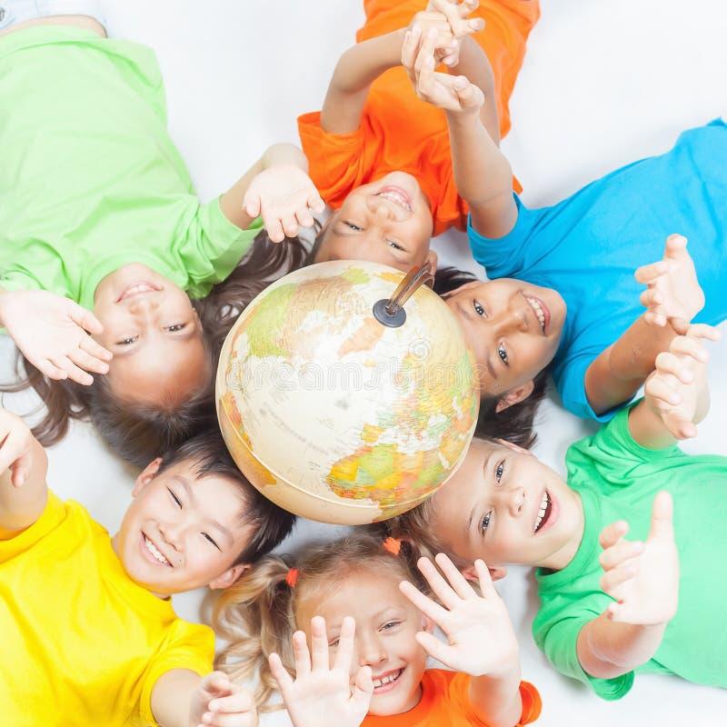 Grupp av internationella roliga ungar med jordklotjord royaltyfri foto