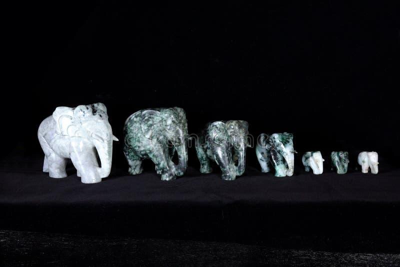 Grupp av jadeskulptur av elefanten som isoleras på svart bakgrund royaltyfri foto
