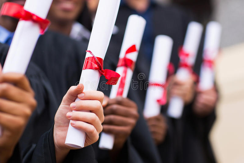 Grupp av kandidater som rymmer diplomet arkivfoton