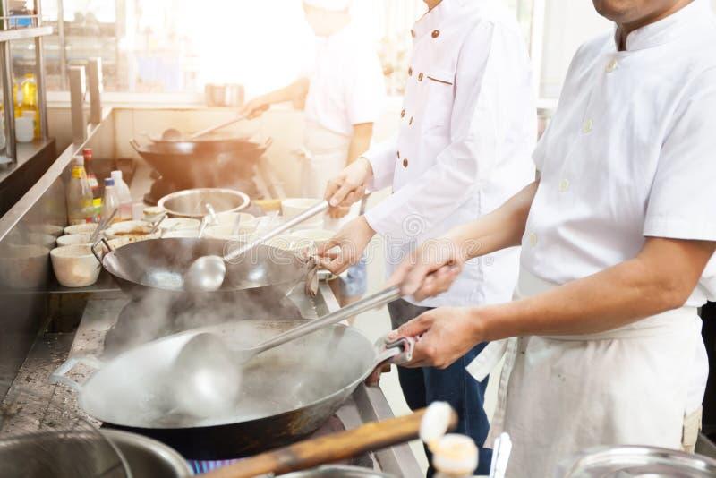 Grupp av kockar i upptagen matlagning för hotell- eller restaurangkök royaltyfria foton