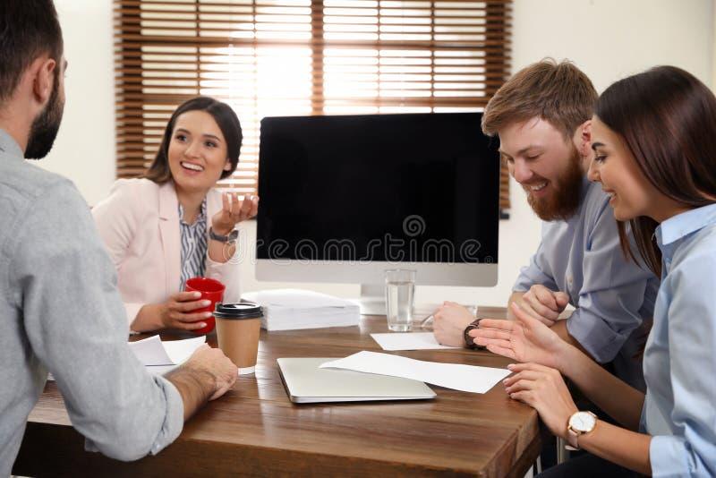 Grupp av kollegor som anv?nder video pratstund p? datoren Utrymme f?r text fotografering för bildbyråer