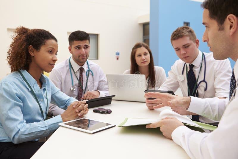 Grupp av konsulenter som sitter på tabellen i sjukhusmöte royaltyfri bild