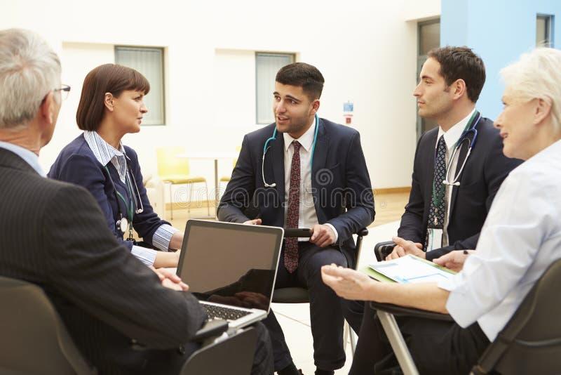 Grupp av konsulenter som sitter på tabellen i sjukhusmöte arkivbild