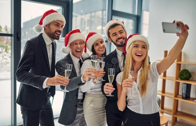 Grupp av kontorsarbetare som firar jul arkivfoto