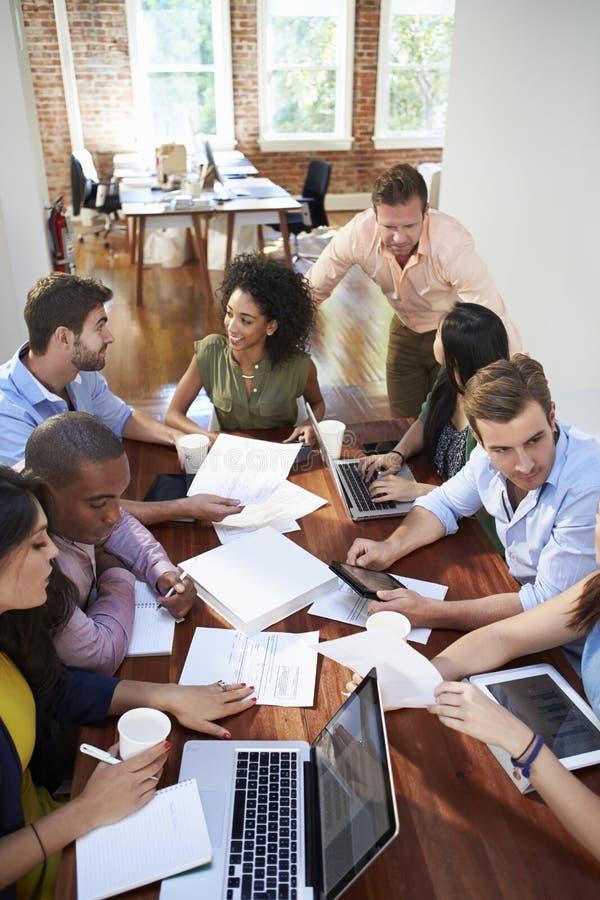 Grupp av kontorsarbetare som möter för att diskutera idéer fotografering för bildbyråer
