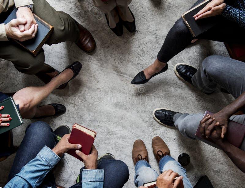 Grupp av kristendomenfolk som tillsammans sitter den läs- bibeln royaltyfri foto