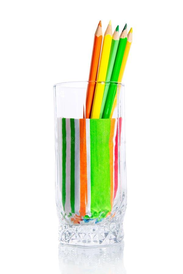 Grupp av kulöra blyertspennor i en glass kopp arkivbilder