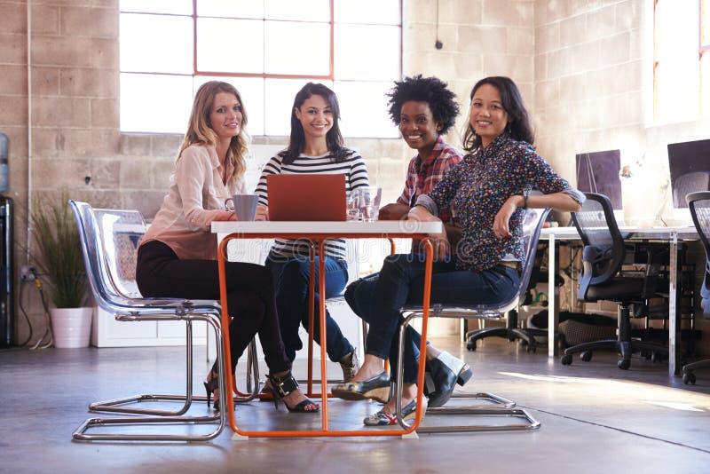 Grupp av kvinnliga formgivare som har möte i modernt kontor royaltyfri foto