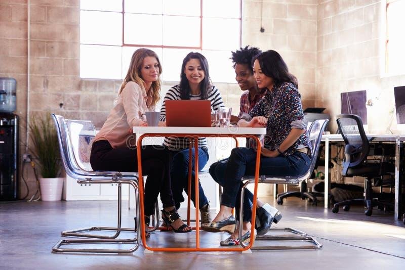 Grupp av kvinnliga formgivare som har möte i modernt kontor arkivfoton