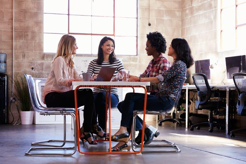 Grupp av kvinnliga formgivare som har möte i modernt kontor arkivbilder
