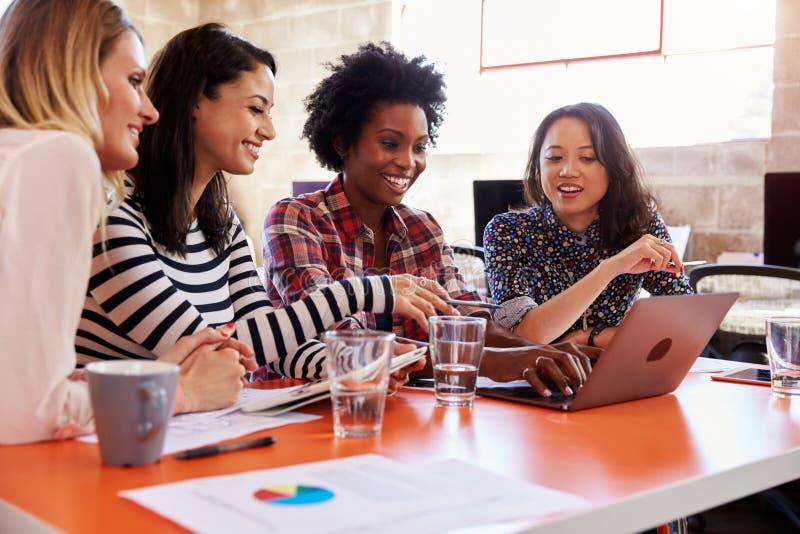 Grupp av kvinnliga formgivare som har möte i modernt kontor arkivfoto