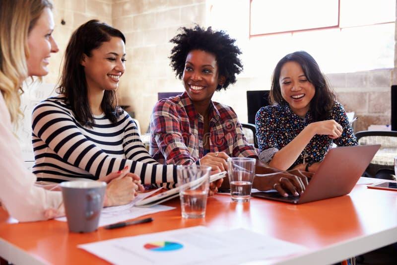 Grupp av kvinnliga formgivare som har möte i modernt kontor royaltyfria foton