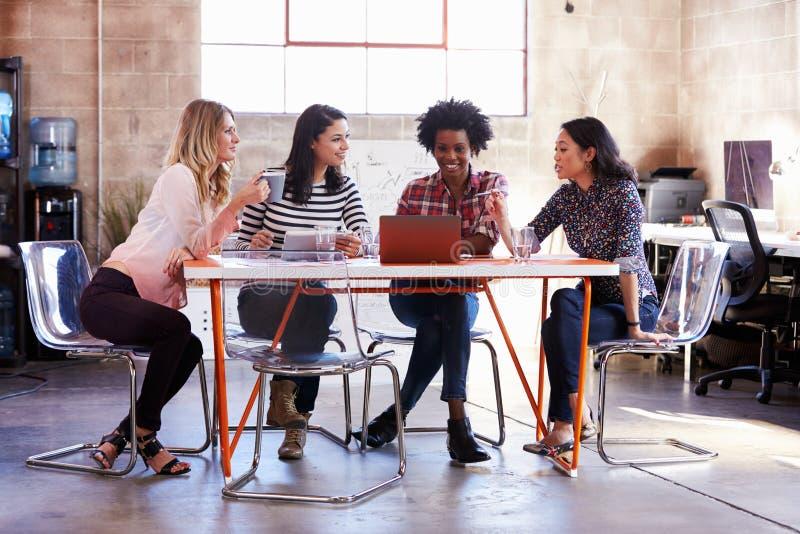 Grupp av kvinnliga formgivare som har möte i modernt kontor fotografering för bildbyråer