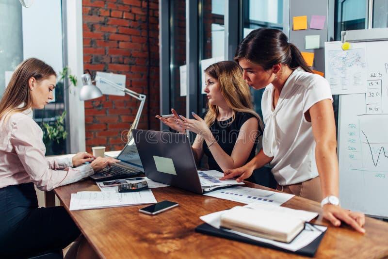 Grupp av kvinnliga ledare som sitter med bärbara datorer och dokument på skrivbordet som samlas för att diskutera problem och pla royaltyfri foto