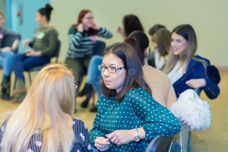 Grupp av kvinnliga studenter för ungt universitet som har en gruppdiskussion som tillsammans sitter på en cirkel av stolar royaltyfri foto