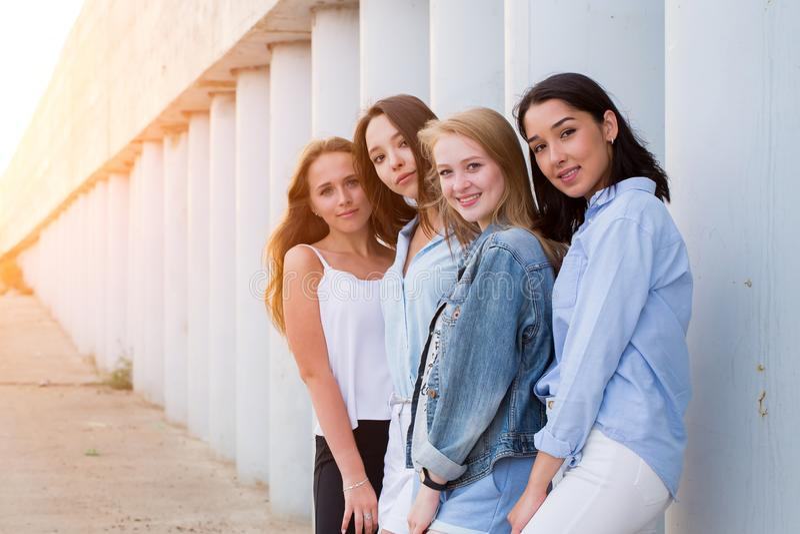 Grupp av kvinnliga studenter som tillsammans poserar utomhus- och ser kameran royaltyfri fotografi