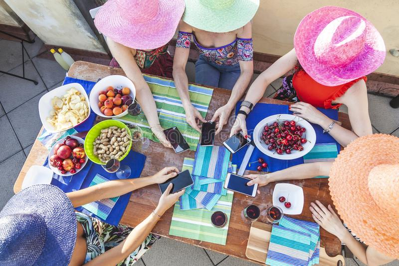 Grupp av kvinnliga vänner som bär färgrika hattar som har rolig böjelse till smartphonen arkivbild