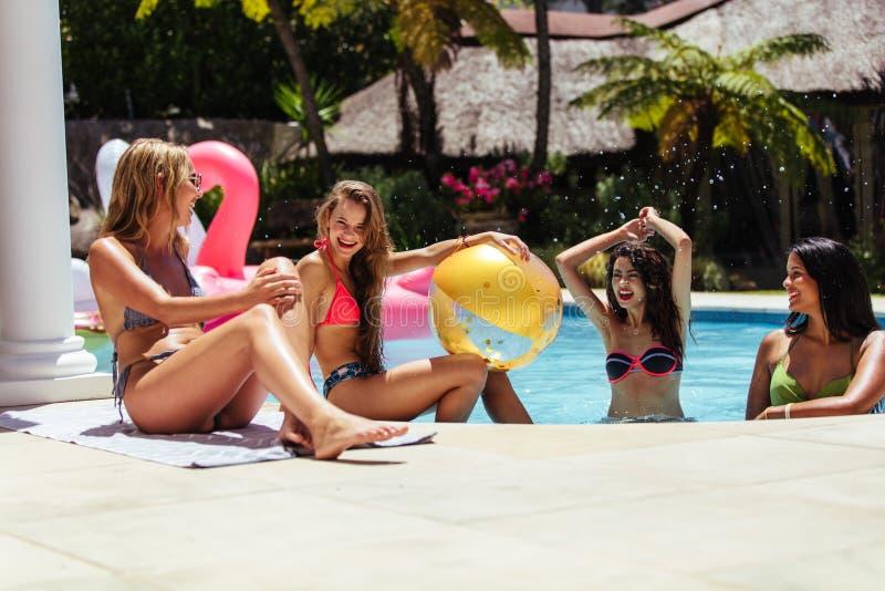 Grupp av kvinnliga vänner som har gyckel i simbassäng arkivfoton