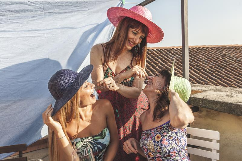 Grupp av kvinnliga vänner som har gyckel, medan äta körsbär på taken fotografering för bildbyråer
