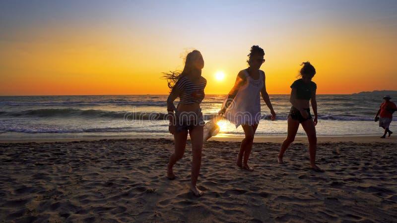 Grupp av kvinnliga vänner som har rolig spring ner stranden på solnedgången arkivfoto