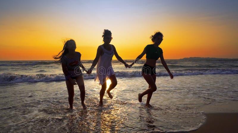 Grupp av kvinnliga vänner som har rolig spring ner stranden på solnedgången arkivbilder
