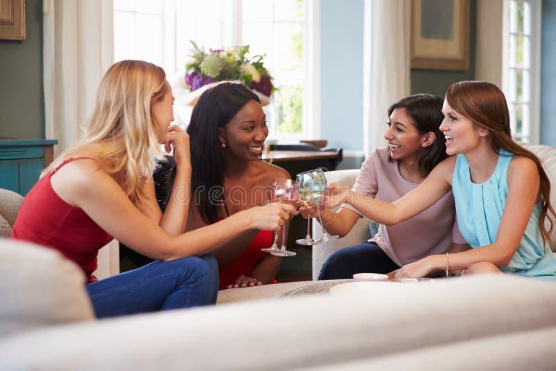Grupp av kvinnliga vänner som hemma kopplar av med drinkar arkivbilder