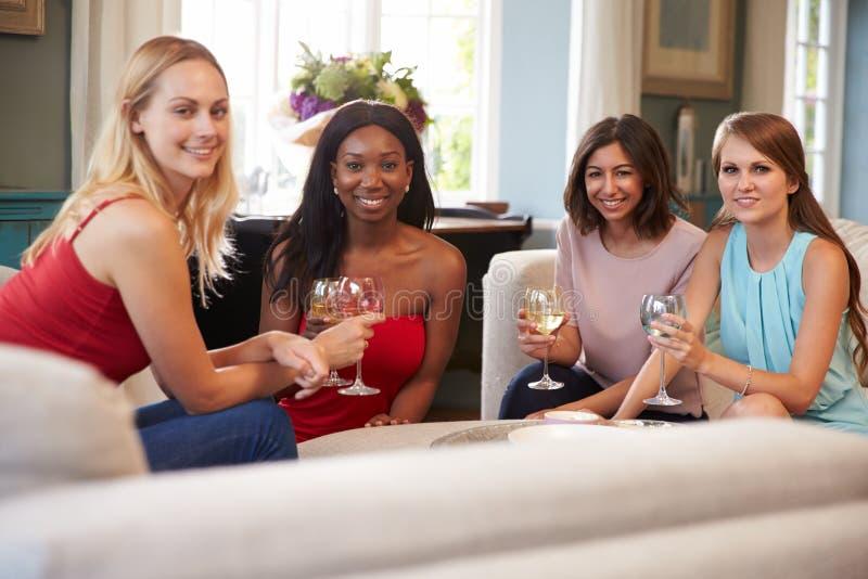 Grupp av kvinnliga vänner som hemma kopplar av med drinkar royaltyfria bilder