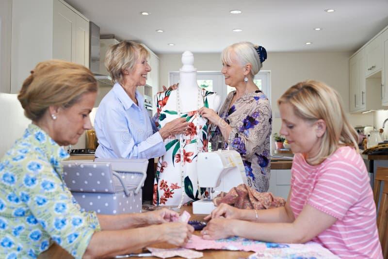 Grupp av kvinnliga vänner som hemma möter för att sy klubban arkivbild