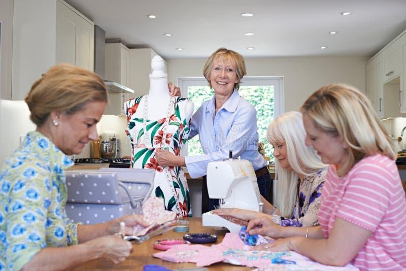 Grupp av kvinnliga vänner som hemma möter för att sy klubban arkivfoton