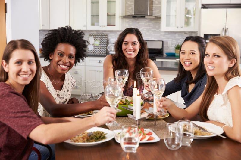 Grupp av kvinnliga vänner som hemma tycker om matställepartiet arkivfoton