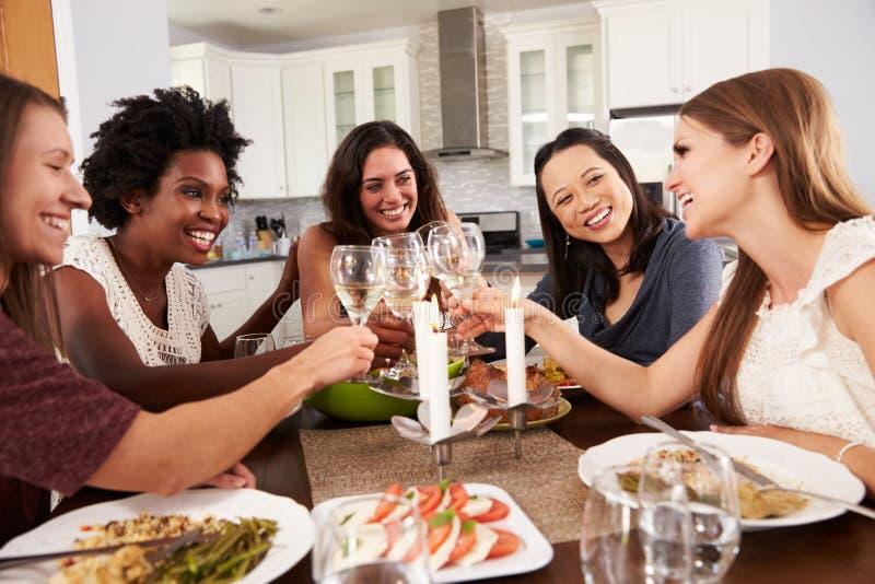 Grupp av kvinnliga vänner som hemma tycker om matställepartiet royaltyfria foton