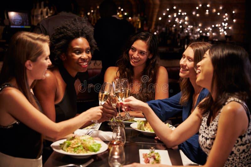 Grupp av kvinnliga vänner som tycker om mål i restaurang arkivbilder