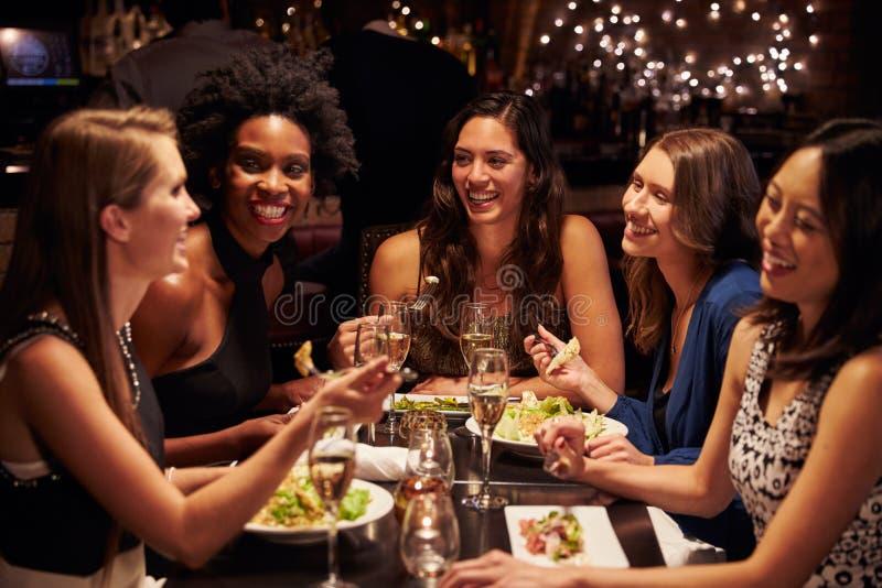 Grupp av kvinnliga vänner som tycker om mål i restaurang royaltyfri bild
