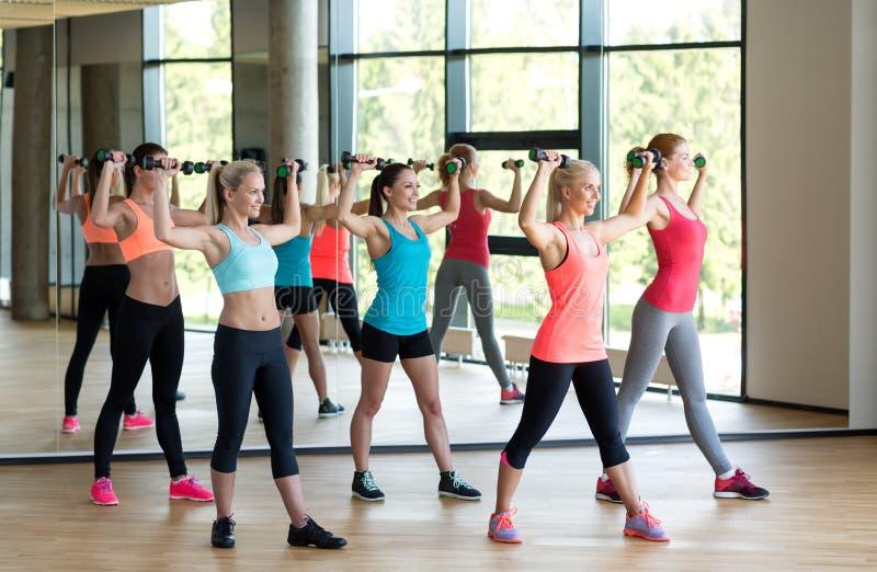 Grupp av kvinnor med hantlar i idrottshall royaltyfri foto