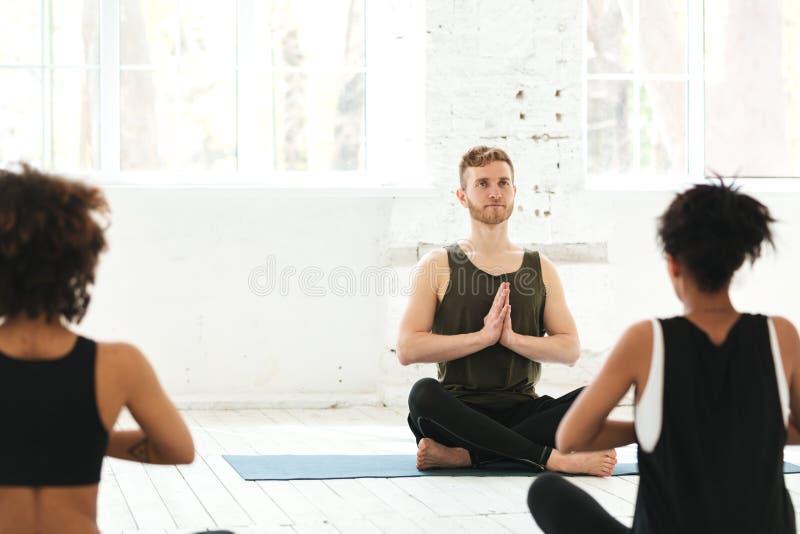 Grupp av kvinnor med manligt instruktörsammanträde på yogamats arkivbild