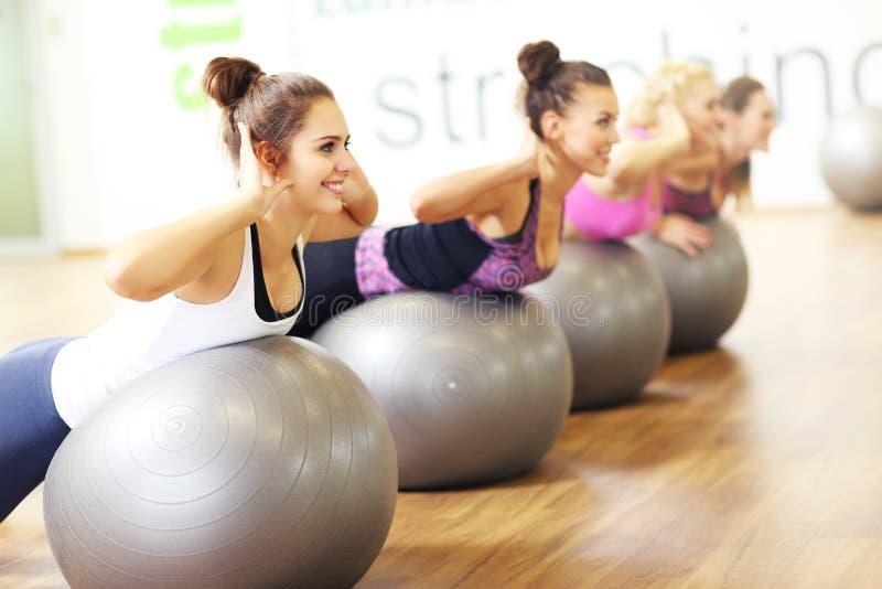 Grupp av kvinnor som övar på bollar i idrottshall royaltyfria bilder