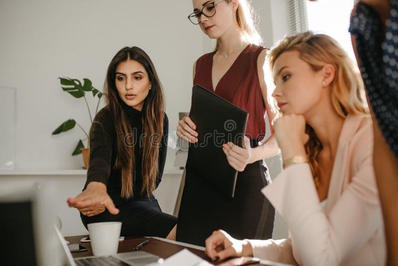 Grupp av kvinnor som diskuterar samman med en bärbar dator royaltyfri fotografi