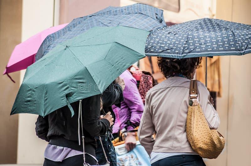 Grupp av kvinnor som går i gatan med paraplyet arkivbild