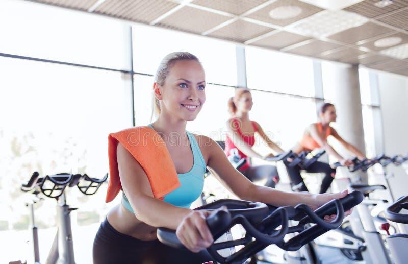 Grupp av kvinnor som rider på motionscykelen i idrottshall arkivbilder