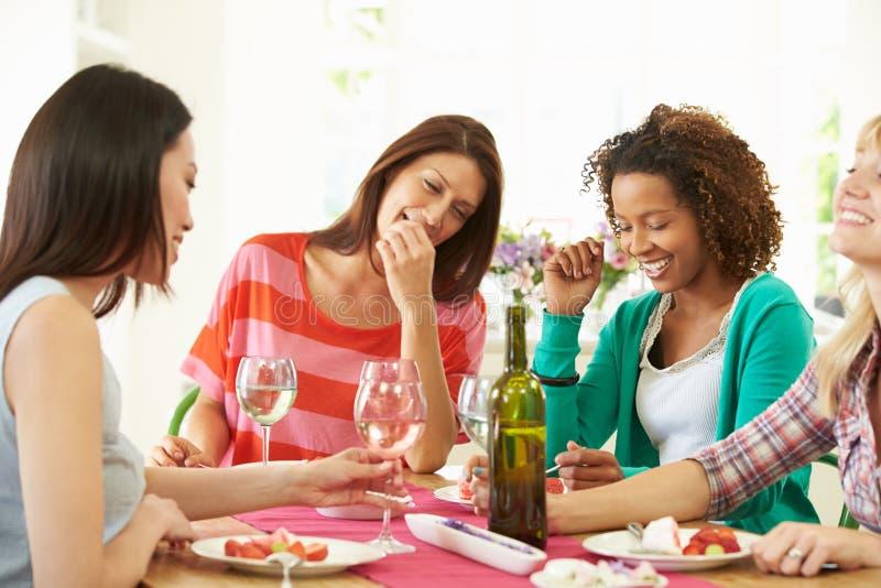 Grupp av kvinnor som sitter runt om tabellen som äter efterrätten arkivfoton