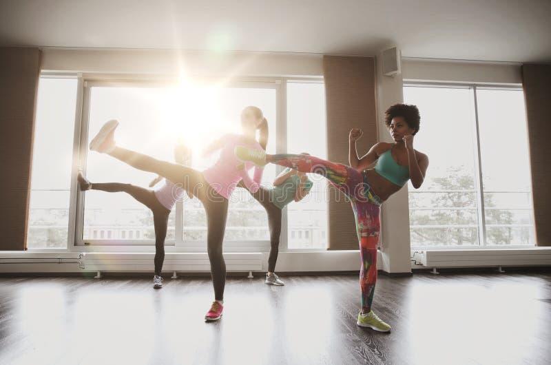 Grupp av kvinnor som utarbetar och slåss i idrottshall arkivbilder