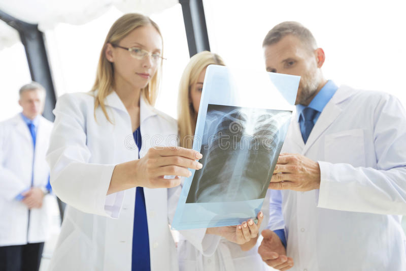 Grupp av läkare med röntgenstrålebildläsning arkivbild