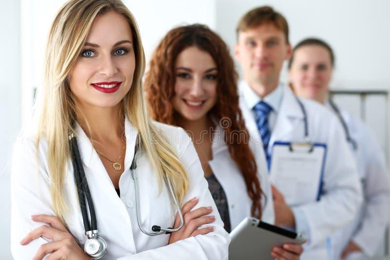 Grupp av läkare som poserar proudly i rad royaltyfri foto