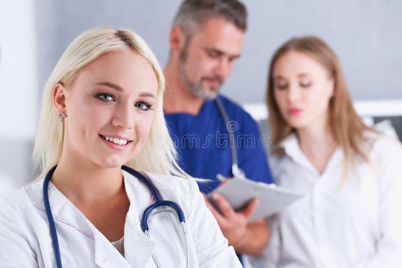 Grupp av läkare som poserar proudly i rad och in camera ser royaltyfri fotografi