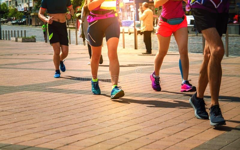 Grupp av löpare som sprintar längs vägen på solnedgången arkivfoton