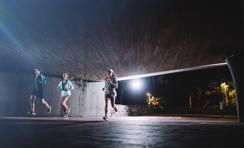 Grupp av löpare som utbildar i staden på natten royaltyfri foto