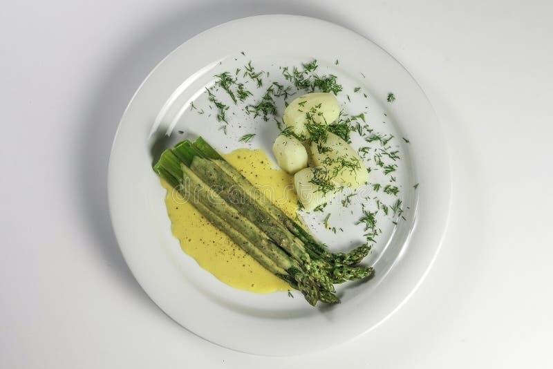 Grupp av lagad mat sparris på den vita plattan med hollandaisesås, potatisar och dill royaltyfri foto